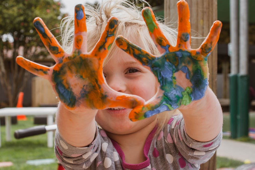 child with paint in her hands
