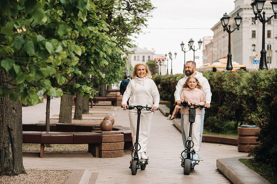 A family rides in electric scooters outdoor