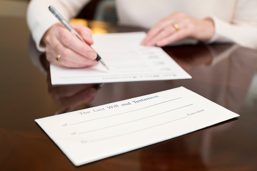 Senior woman signing her last will and testament
